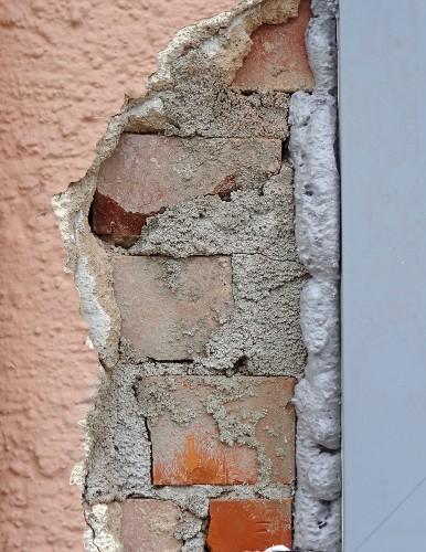 Sanierungsfall: Der abgeplatzte Außenputz bringt Ziegelsteine mit Mauerputz zum Vorschein