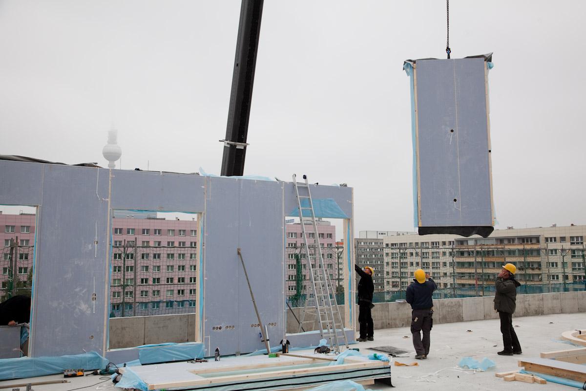 """Vormontierte Leichtbauwände – wie hier beim """"e-Wohnhaus""""-Objekt in der Nähe des Berliner Alexanderplatzes – werden per Kran auf das Dach transportiert. Foto: Knauf"""