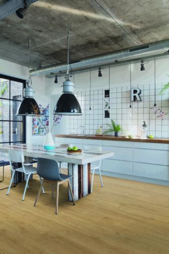 Feuchtraumlaminat macht es möglich: So lässt sich ein wohnlicher Holzdielen-Look auch kostengünstig in der Küche realisieren. Foto: Quickstep – Premium brand by Unilin