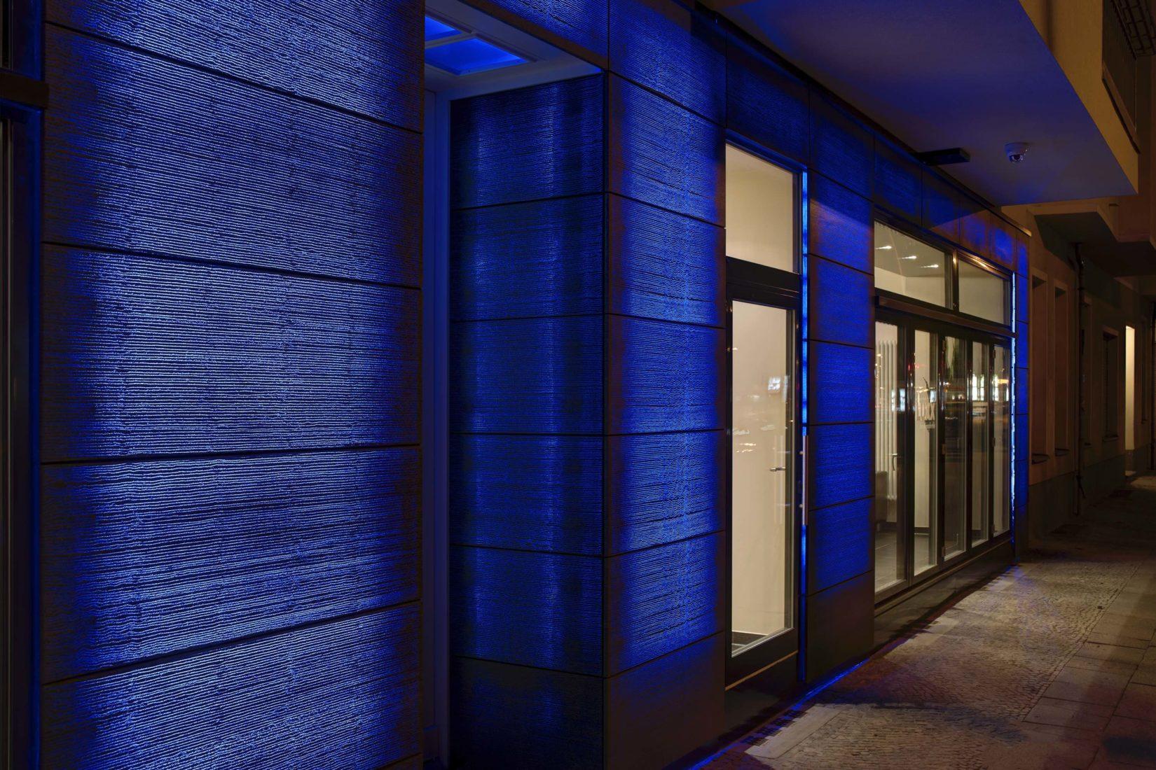 Rückseitig beleuchteter Lichtbeton an einer Hausfassade. Foto: Lucem Lichtbeton