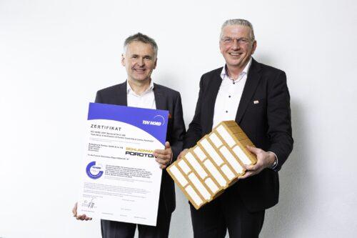 Johannes Edmüller von Schlagmann Poroton (l.) und Clemens Kuhlemann von der Deutschen Poroton präsentieren den T7 und das Zertifikat des TÜV-Nord. Foto: Deutsche Poroton, Christoph Große