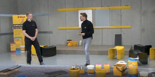 Fliesenleger-Weltmeister Janis Gentner (l.) führt unter anderem den neuen Fliesenkleber vor.